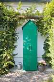 Closed green garden cupboard with gable roof below climber-covered pergola