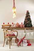 Pendant lamp above festively decorated rustic wooden ceiling, vintage chair and Christmas presents wrapped in red and white paper