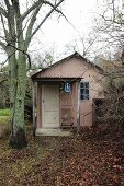 Simple garden shed made from painted corrugated metal with petroleum lamp in porch in autumnal garden