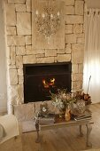 Ornaments on vintage wooden footstool in front of fire in stone fireplace