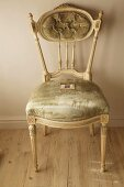 Elegant, antique Rococo chair with pastel green velvet cover and carved elements