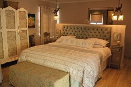 Beige patterned bedspread on double bed with button-tufted headboard against half-height well in rustic bedroom with subdued lighting