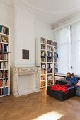 Stucco ceiling, children using laptop sitting on black sofa and bookcases in living room in period apartment