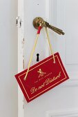 'Do not disturb' sign on traditional brass door handle