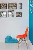 Classic orange shell chair below collection of butterflies in display cases on wall