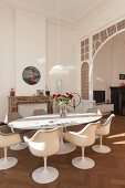 Tulip armchairs around vase of roses on oval table in front of traditional arched doorway with lead glazing