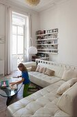 Girl playing in front of white leather sofas in living room