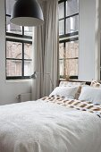 Bed with view of neighbouring building through lattice windows