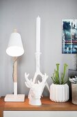Scandinavian-style still-life arrangement of table lamp and white accessories