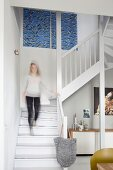 Woman walking down staircase into living room