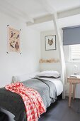 Einzelbett mit rot-weiß gemustertem Plaid in Zimmerecke mit weißer Holztragwerk-Konstruktion