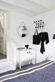 View across grey blanket on bed to white cabinet next to doorway with wooden steps and classic black Hang-It-All coat rack