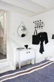Blick über Bett mit Tagesdecke auf weisses Schränkchen neben Durchgang mit Holztreppenstufen und schwarze Klassiker-Garderobe