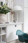 Blumenstrauss und weisse Tischleuchte auf weissem Sideboard, davor türkisfarbener Schalenstuhl im Klassikerstil