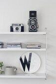 Retro-Fotoapparate und CD-Hüllen auf weißem String-Regal mit schwarz-weißem Wandteller