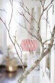 Pink paper pompom on bare branch