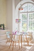 Hand-made pastel decorations on breakfast table in front of arched lattice window in period apartment