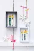 Stylised candles made from rolled banknotes in picture frames as Christmas presents