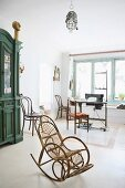 Rattan rocking chair in bright room with sewing machine in background