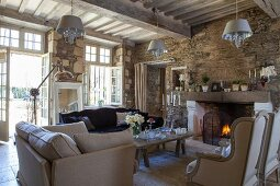 Elegant armchairs in front of open fire and open terrace doors in living room of rustic country house