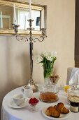 Silver candlestick and vase of tulips on round breakfast table