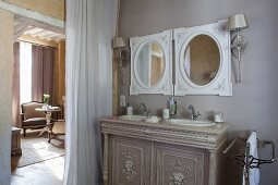 Elegant washstand with twin inset sinks below round mirrors next to curtain in doorway