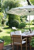 Gedeckter Tisch unter Sonnenschirm in gepflegtem Garten