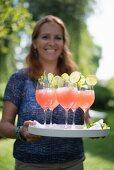 Fröhliche Frau serviert Erfrischungsgetränke auf Tablett im Garten