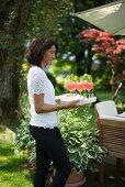 Frau serviert Erfrischungsgetränke auf Tablett im Garten