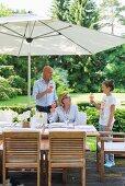 Drei Personen mit Erfrischungsgetränken am Tisch im Garten