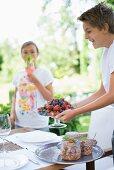 Lachender Junge hält Glasschale mit frischer Beeren, auf Gartentisch Tablett mit Einmachgläsern
