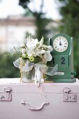 Bouquet of white flowers with orchids next to vintage-style, wooden perpetual calendar