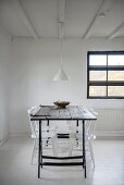 Schlichter Essplatz mit weiss lackierten Stühlen um Tisch, Holzplatte auf Metallböcken
