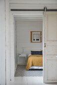 Offene Schiebetür und Blick auf Bett in schlichtem Schlafzimmer mit weisser Holzwand