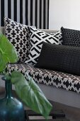 Scatter cushions with geometric, black and white patterns on sofa