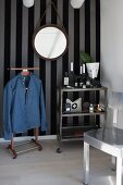 Denim shirt hung on valet stand next to serving trolley below round mirror on striped wallpaper