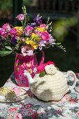 Colourful bouquet, petit fours and teapot in crocheted tea cosy on floral tablecloth