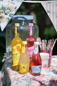 Bottles of juice, paper cups and drinking straws on garden table with floral tablecloth in sunshine