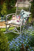 Weathered, comfortable cane rocking chair next to bed of forget-me-not in summery garden