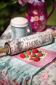 Vintage-style arrangement of rolling pin with written motto and crocheted strawberries on tablecloth on garden table