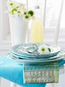 Tellerstapel mit Gabeln und weisser Blume auf weissem Stuhl
