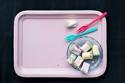 Colourful marshmallows on pink tray