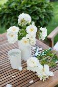 weiße Rosen in Vase und daneben auf einem Gartentisch