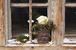 Mit Wachs beträufelter Pflanztopf dekoriert mit Rose, Efeu und Zapfen