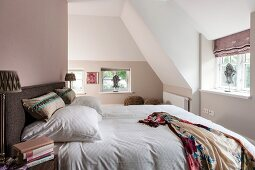 Double bed in bedroom with pastel walls in converted attic