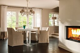 Pale, loose-covered chairs at round white table below chandelier: fire in fireplace to one side