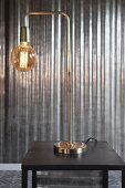 Elegant brass table lamp with glass lampshade in front of shiny metal wall