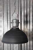 Black industrial-style lampshade against shiny corrugated metal wall