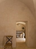 Sparsely furnished, vaulted Mediterranean interior with stone floor and view of sofa with blanket through open doorway