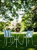 Cushions on two spindly metal chairs at round table on lawn in garden
